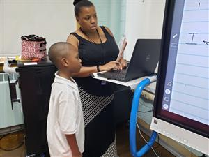 3rd Grade teacher, Ms. Hughley talks with student at workstation