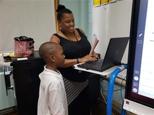 3rd Grade teacher, Ms. Hughley smiles listening to student at workstation