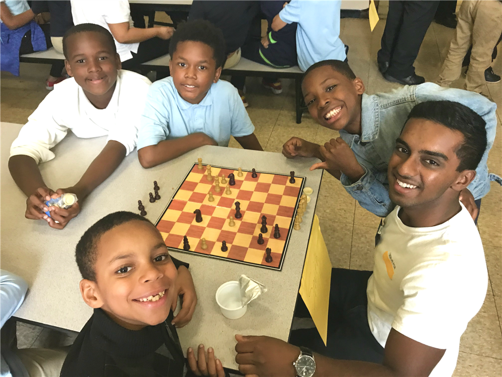 Students sitting around a staff member smiling and playing chess