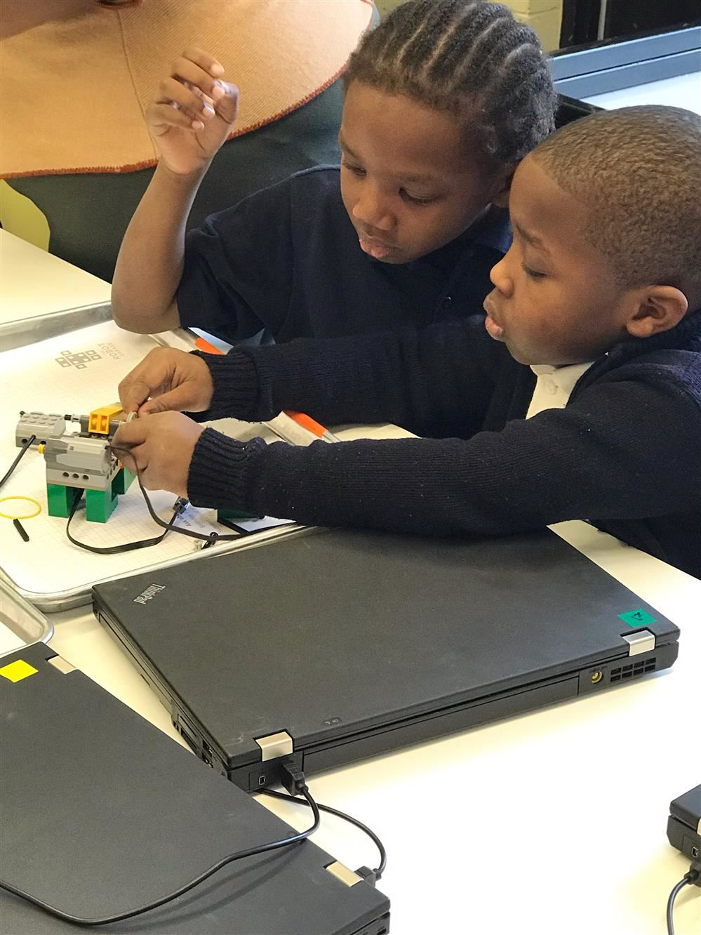 kindergarten students build a robot with computers and connect blocks