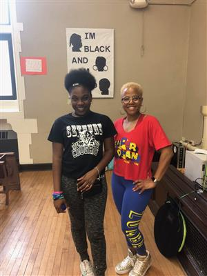 "Student stands with Zumba instructor. Poster behind them says ""I'm black and I'm proud"""
