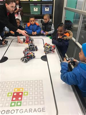 Kindergarten class play with robots using remote controls