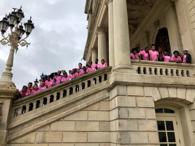 Girls stand at the Michigan State Capitol steps
