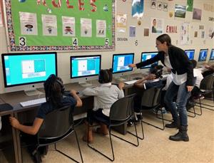 Ms Ally assists students during Hour of Code