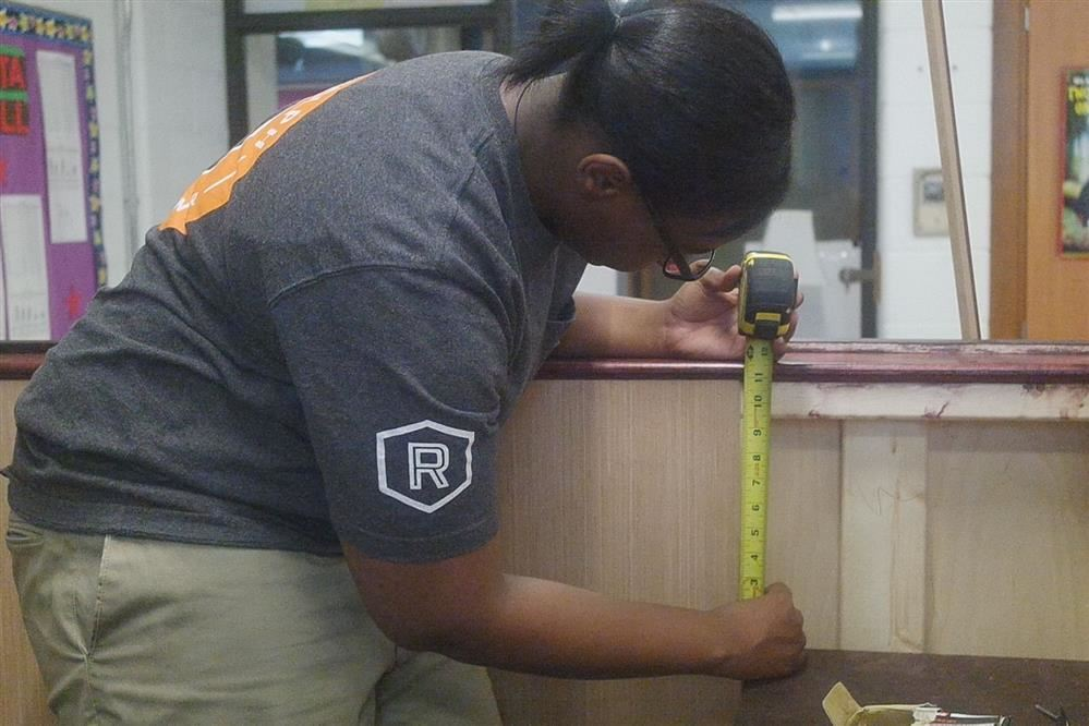 Student measuring height for court bench