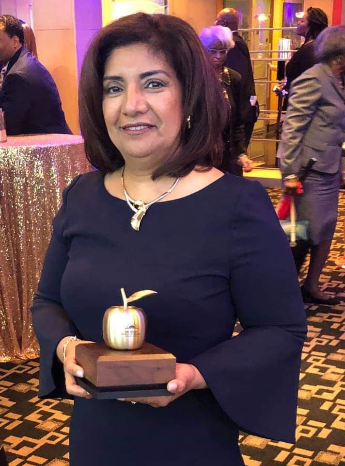 Principal of the Year Mrs. Martinez holding golden apple award