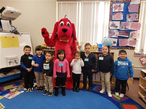 PreK students standing in front of Clifford the Big Red Dog in a Prek Classroom