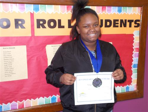 Sixth grade student wearing medal and holding reward for art