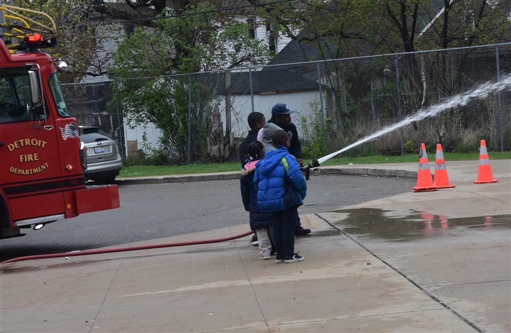 Two students look on while one student holds a large water hose with fireman.
