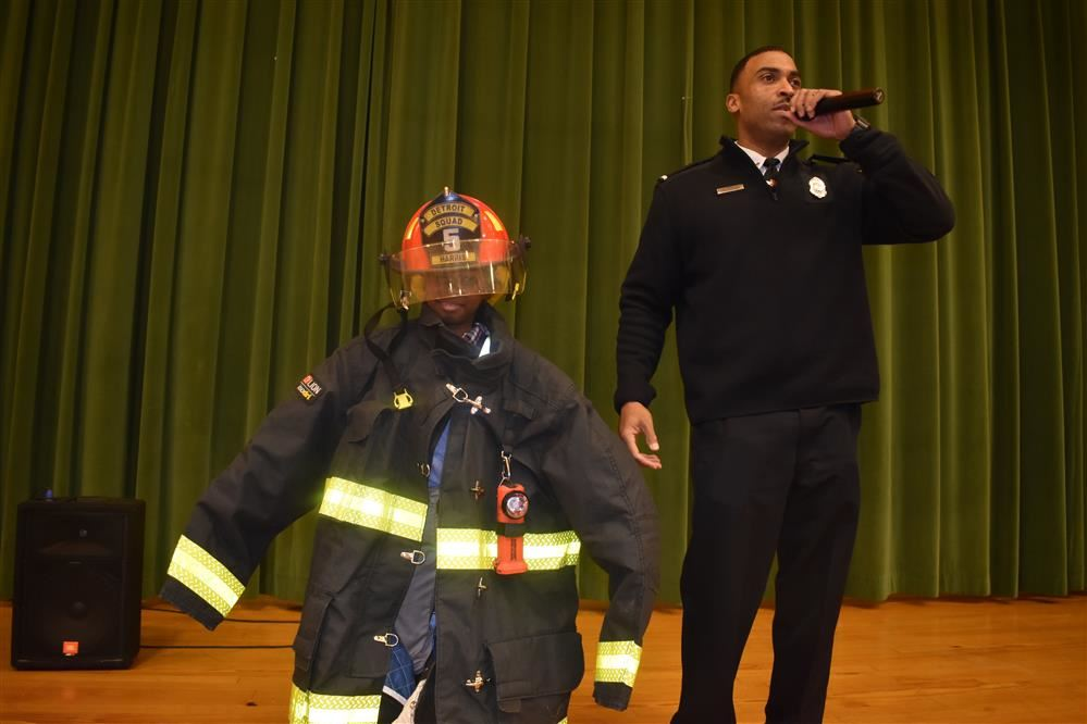 First grade girl dressed as a fire fighter with Lt. Harris