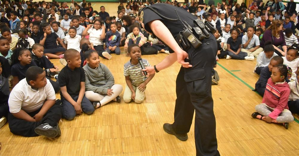 Student speaks into microphone held by Detroit Public Schools Community District  officer J. Hudock