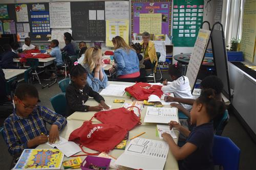 Volunteers from Quicken Loans work with first grade students