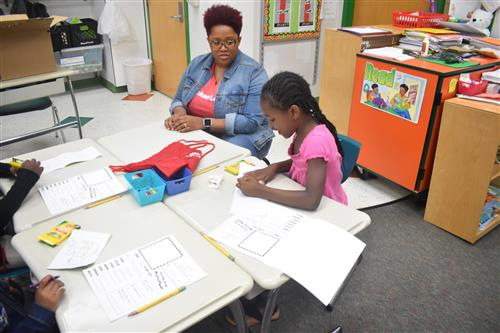 Volunteer sits at desk with first grade student