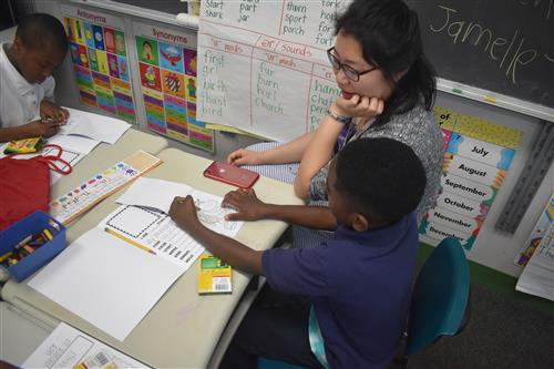 Tutormate volunteer sits at table with first grade student