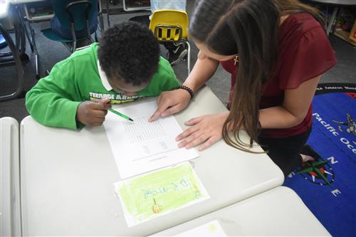 Volunteer from Tutormate work with first grade student on word search