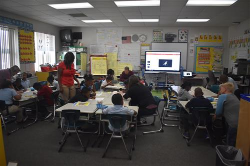 First grade teacher and Tutormate volunteers from Lear work with first grade students