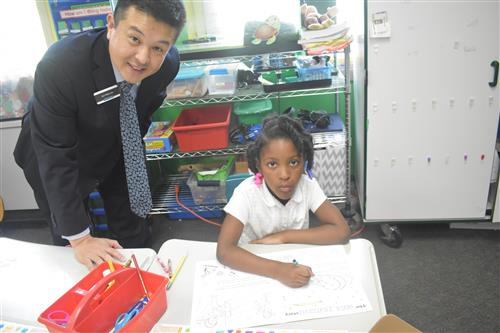 Comerica Bank volunteer stands by first grade student