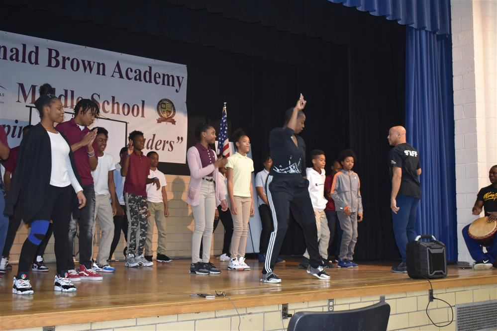 Middle school  students on stage with dance instructor