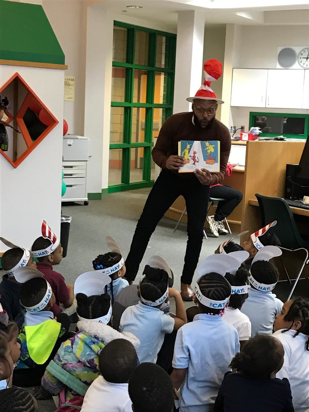 Principal Pitt show a group of Kindergarten students a picture while reading a Dr. Seuss story.