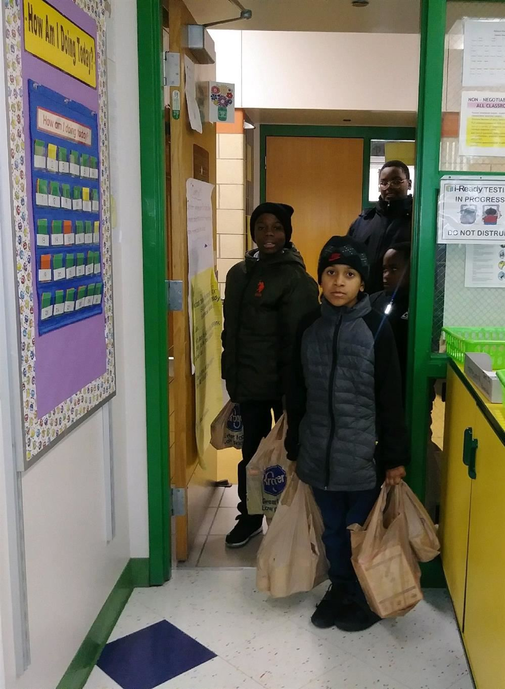 Students standing in doorway carrying food donations in bags.