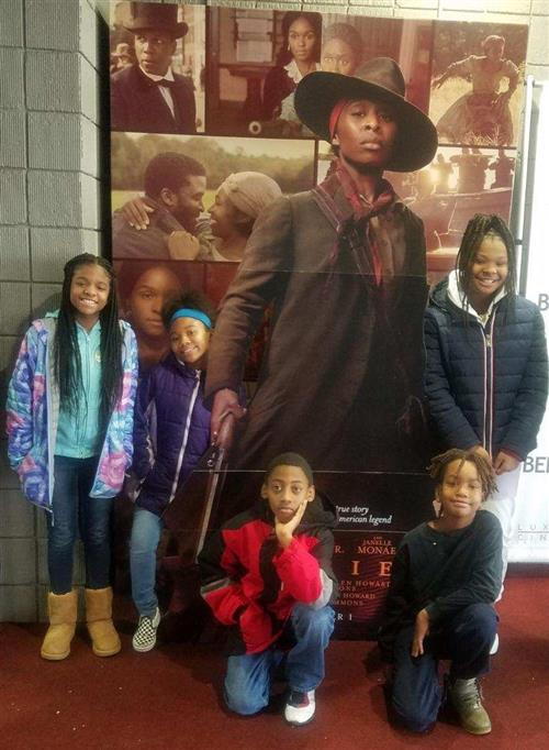 Students stand in front of the Harriet poster at the theater.