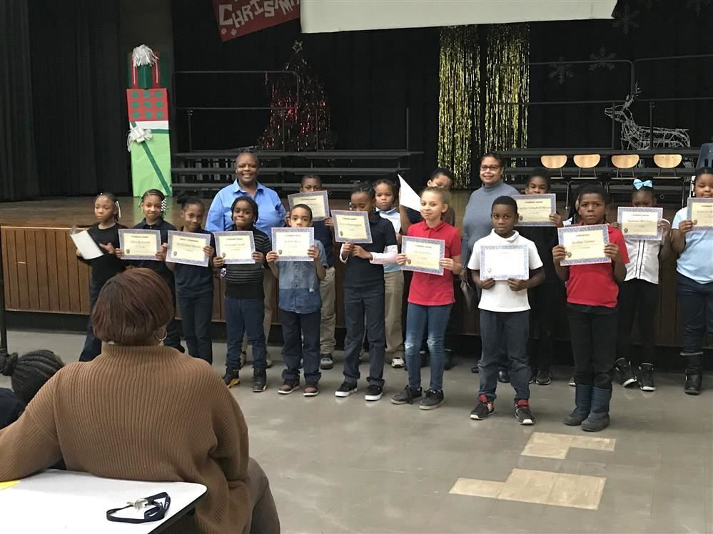 Students holding certificates for honor roll and citizenship