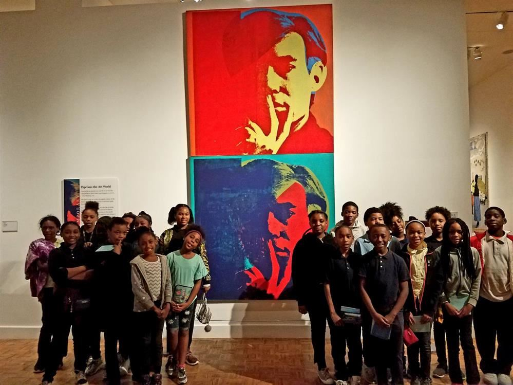Students standing in front of a painting