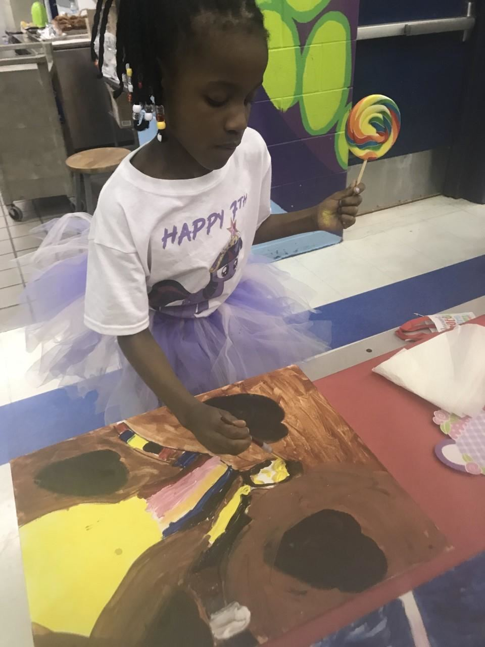 Girl student painting while holding a lollipop