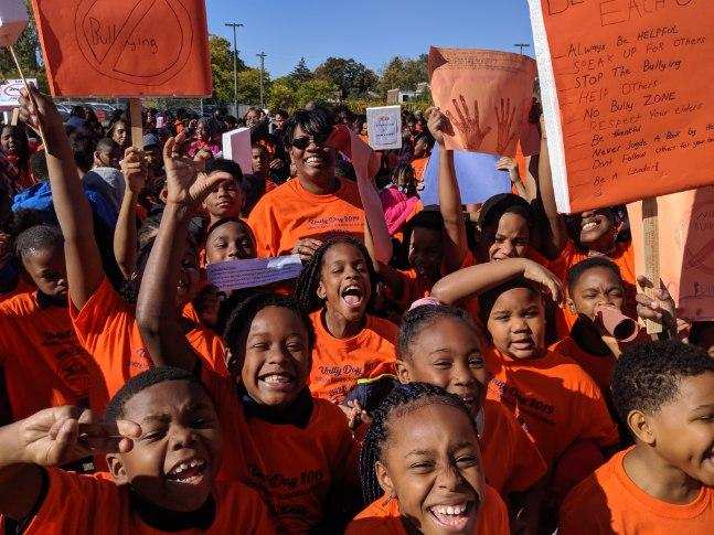 Adult with students wearing orange shirts and holding anti bullying signs