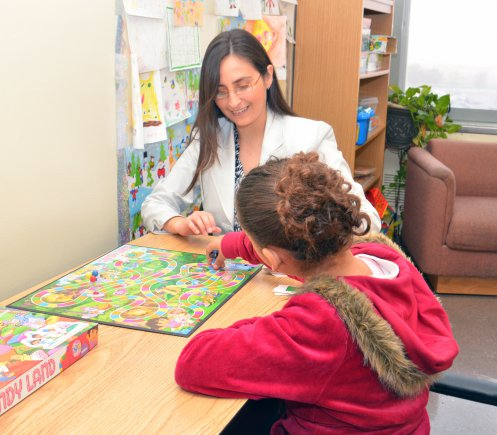 A woman playing a board game with a little girl