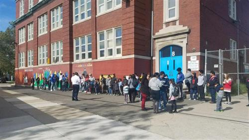 students and parents in line in front of the school waiting to travel