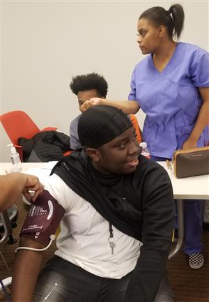 Adult Education West student D'Airre Little getting his blood pressure taken by a Ben Carson HS student.