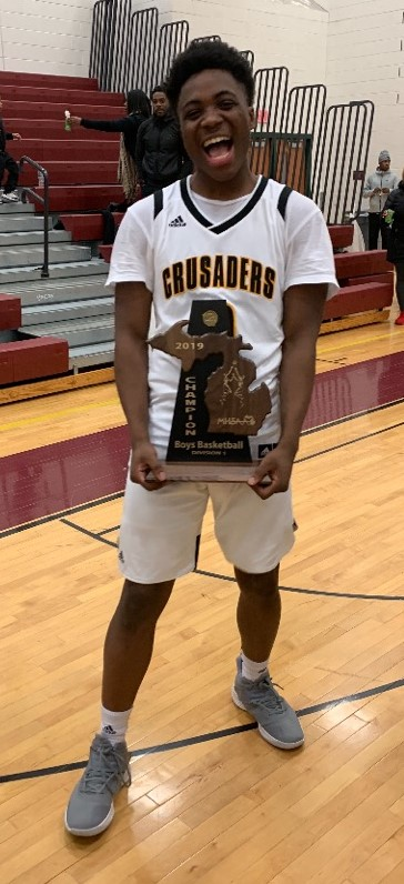 King Crusader Boys Basketball Player holding District Champion trophy