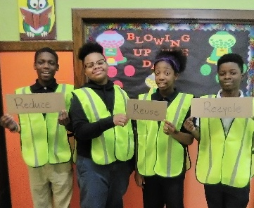 Four students in neon vest holding signs.