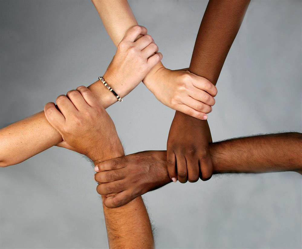 Arms of different skin colors holding onto each other