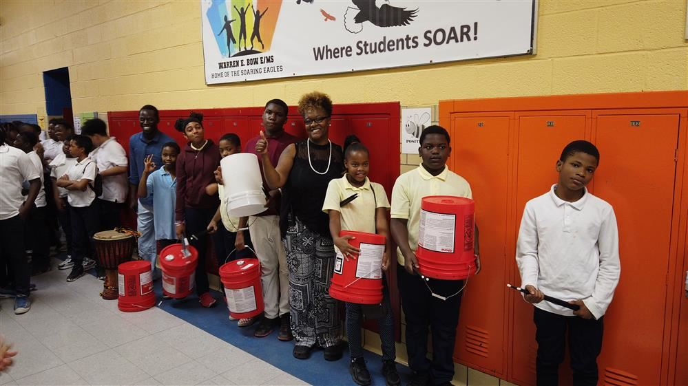 students holding drum bucket