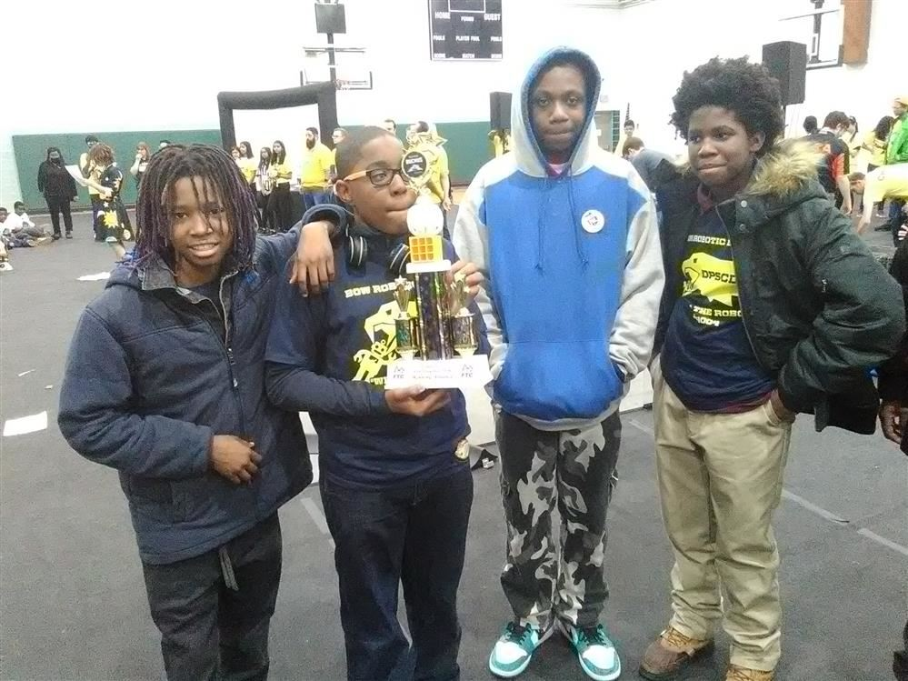 Students holding a robotic trophy