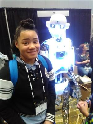 student standing next to robot
