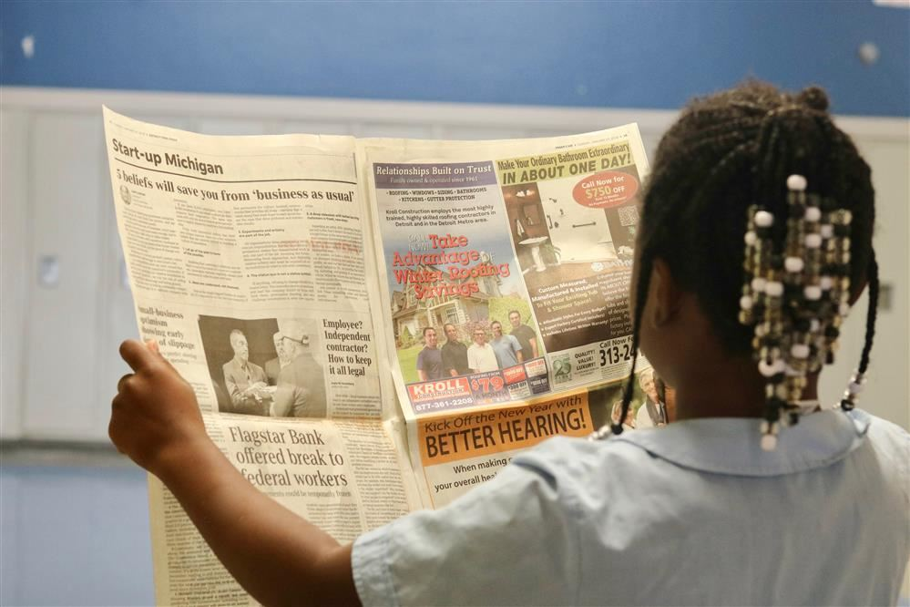 Image of a student reading the newspaper