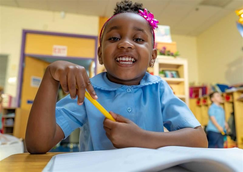 Image of a student sitting happily at her desk