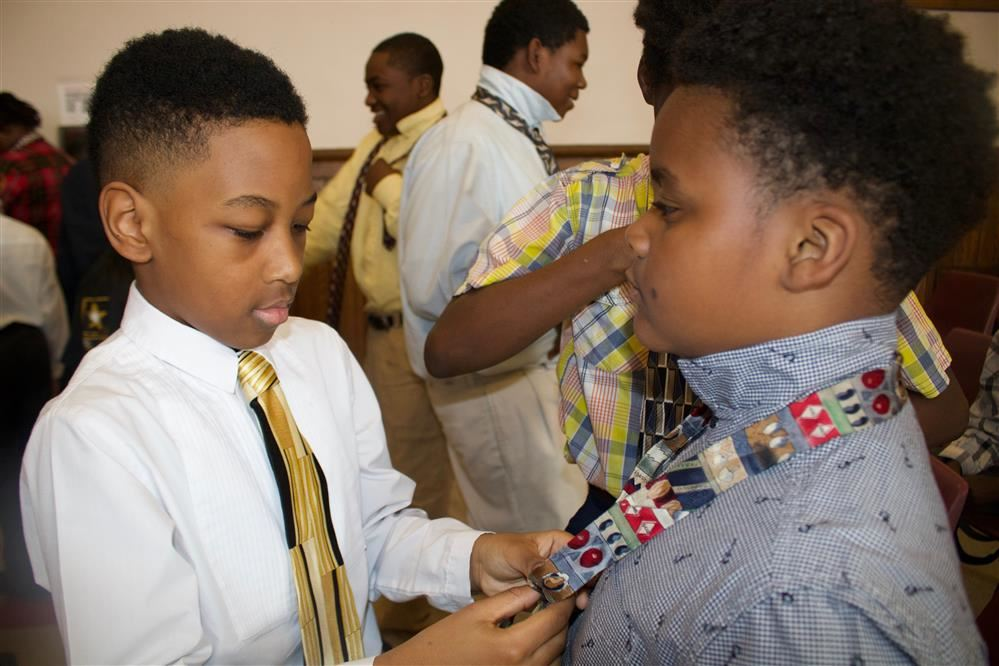 Student helping another put on a tie