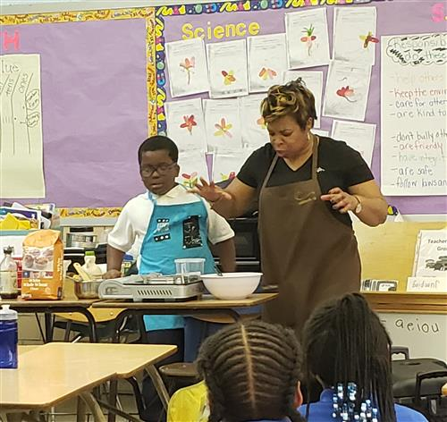 a student works next to a chef to learn about cooking
