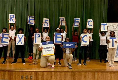 Students standing and kneeling holding letters that spells Expect Respect