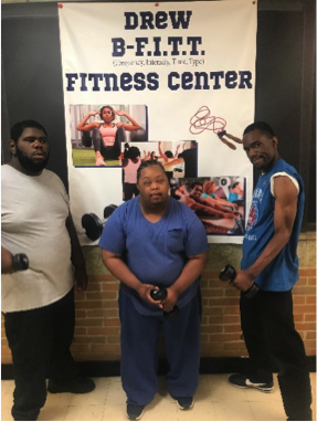 Three male students standing in front of  fitness poster