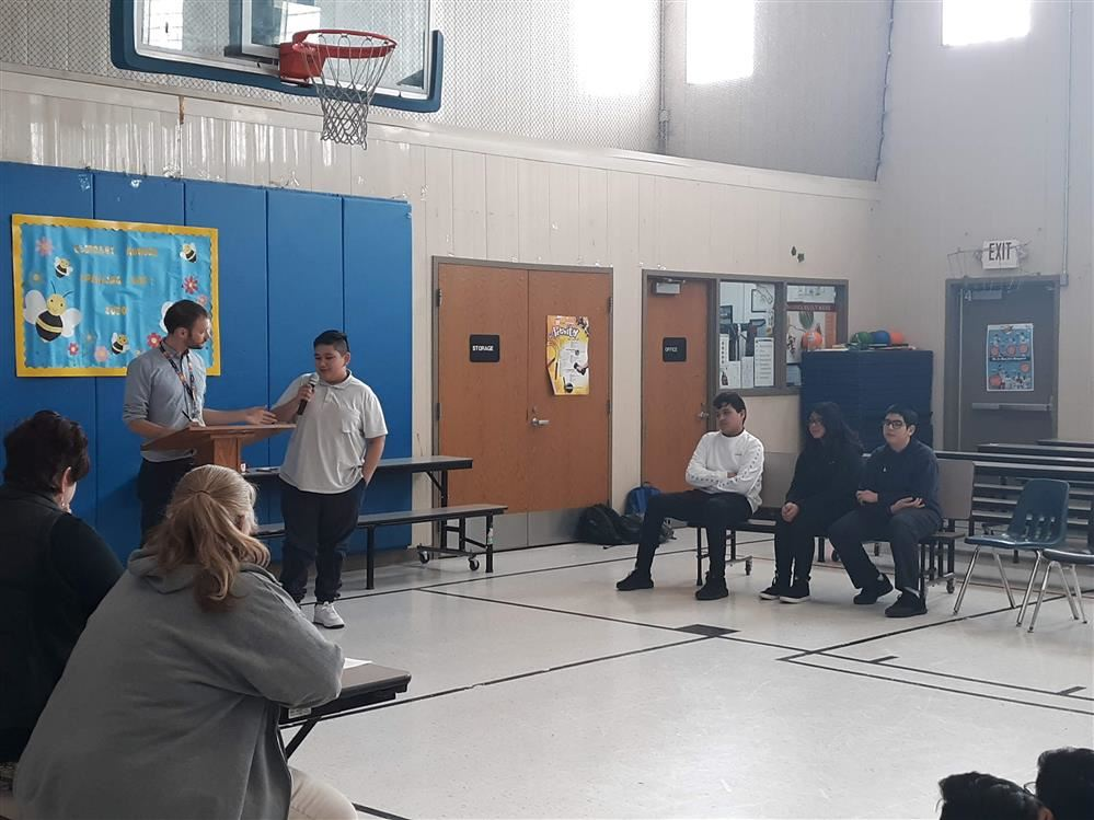 students participating in the spelling bee while a teacher tells the word