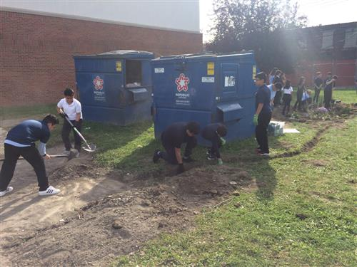 students digging a trench for a new rain garden