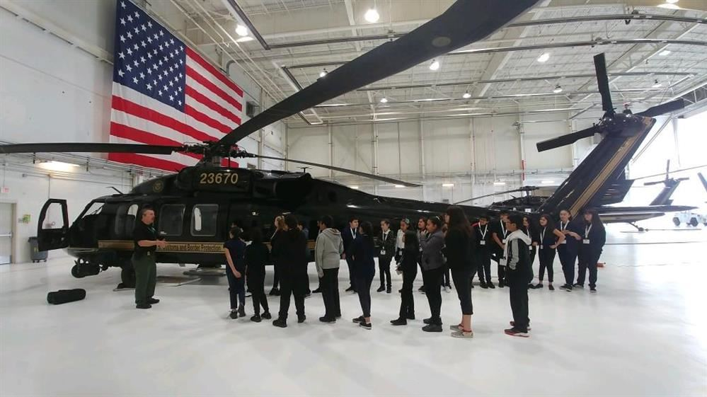 students and an adult standing in front of a helicopter