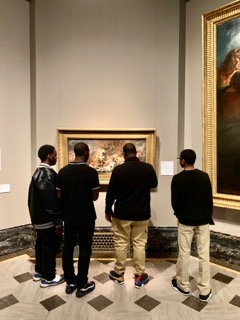 Students and staff member admiring art.