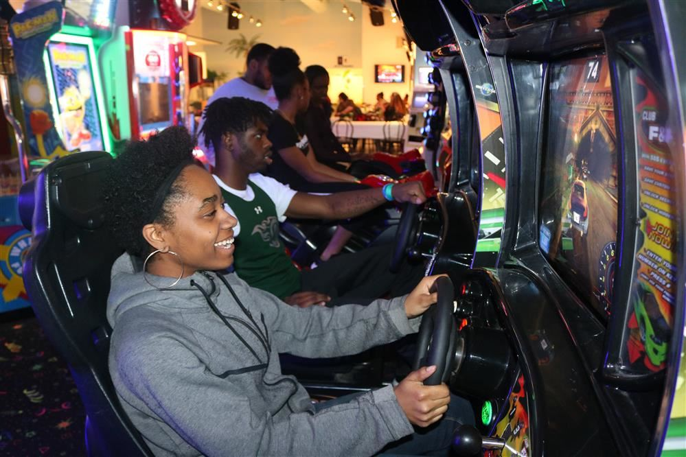 Two seniors battle it out on some arcade race games at Paradise Park