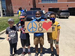 Image of children holding hand made sign with Peace and Love symbols
